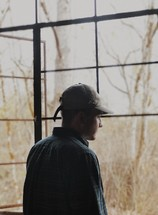 a man in a ball cap looking out a window