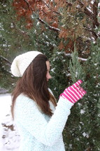 teen girl touching snow on bush with gloves on