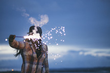 A woman holding a fiery sparkler before her in the evening.