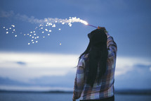 A woman holding a fiery sparkler against the evening sky.