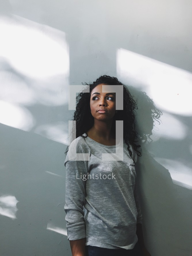 Woman leaning against a wall.