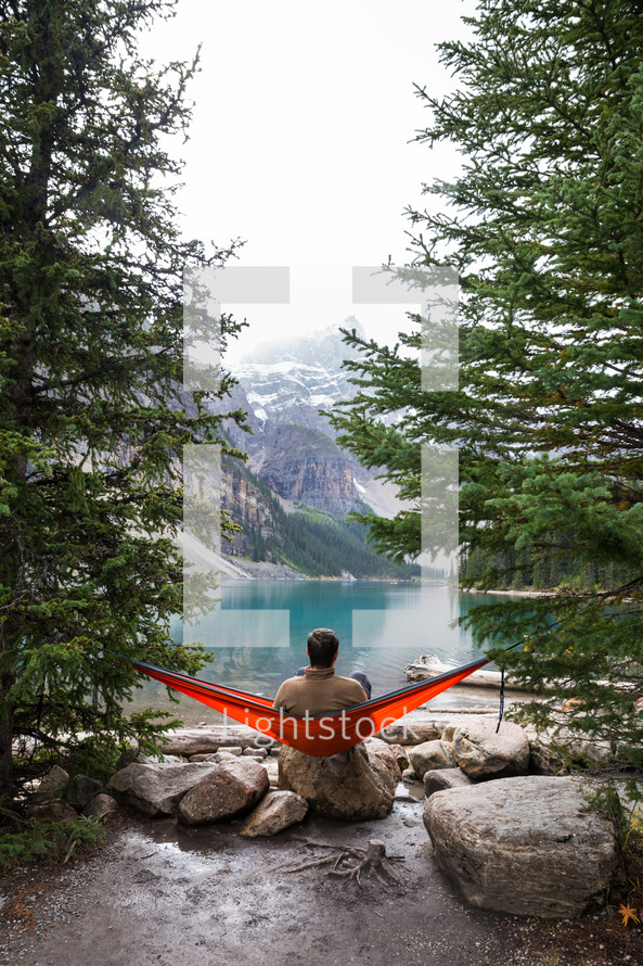 man in a hammock at a lake shore