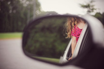 child's curls in a rearview mirror