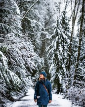 a woman standing in a winter forest