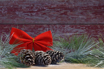 red bow, pine cones, and Christmas greenery