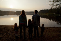 a young family holding hands on a lake shore at fall
