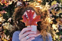 a woman holding a fall leaf