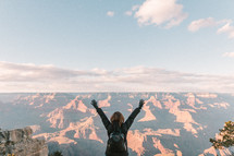 a woman standing at the edge of a cliff in front of canyons with arms raised