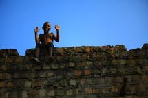 African boy sitting on stone wall