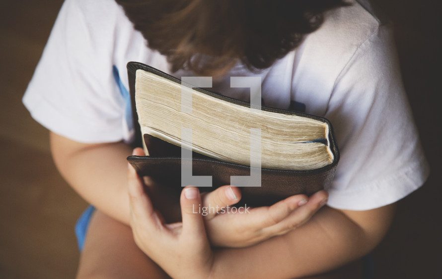 child holding a Bible