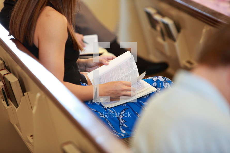 a woman flipping through a Bible while sitting in a church pew