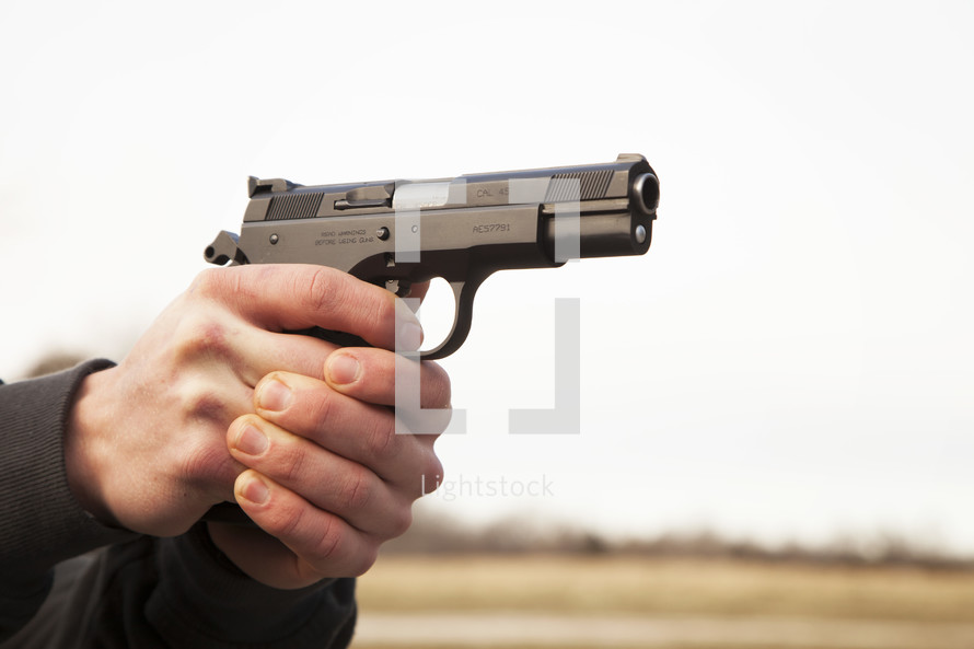 A man's hands holding and aiming a handgun.