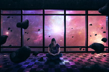A woman lost in her Bible as a space scene surround her