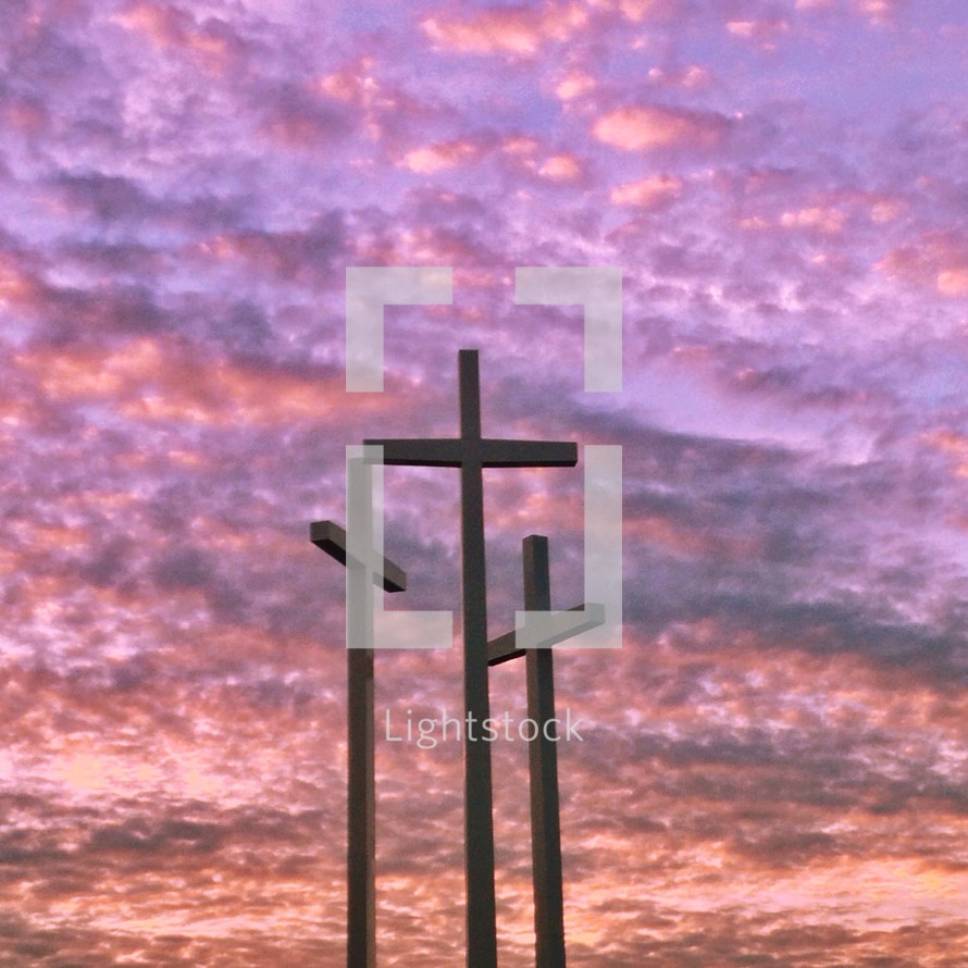 Three crosses under a purple cloudy sky.