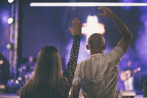 couple with raised hands at a worship service