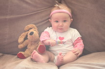 """Baby girl posing with her teddy bear on Father's Day wearing T-shirt that reads, """"I love daddy."""""""