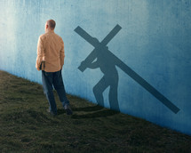 a man carrying a Bible and a shadow of Jesus bearing a cross