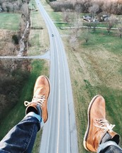 dangling feet and aerial view above a rural highway