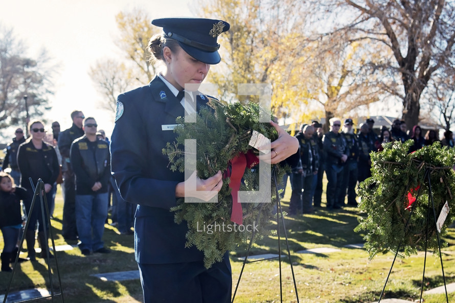 Solider with a wreath in a cemetery