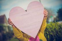 a child's hands up a wooden heart