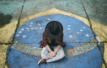 a teen sitting on a painting of Brazil's flag