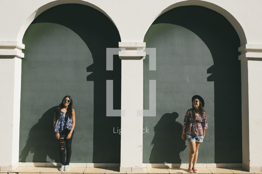 young women posing in front of a building