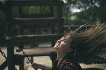 teen girl on a swing in a playground