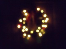 The glowing lights of a Christmas wreath light up the night from a distance bringing warmth, light and festive cheer to the winter nights during the time of Celebration we call Christmas.