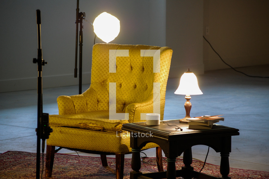 Chair with a table and lamps on a rug.
