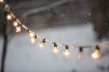 falling snow and a string of glowing lightbulbs
