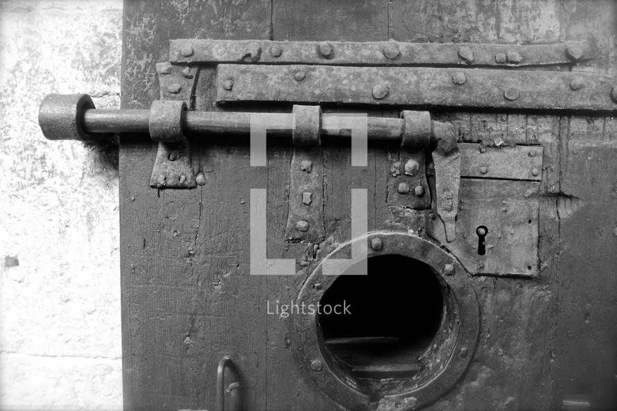 ancient prison door with bolt window and lock