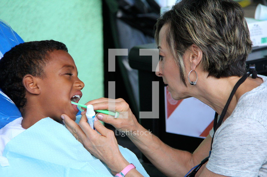 woman brushing a child's teeth