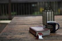 Bible, coffee mug, and lantern on picnic table
