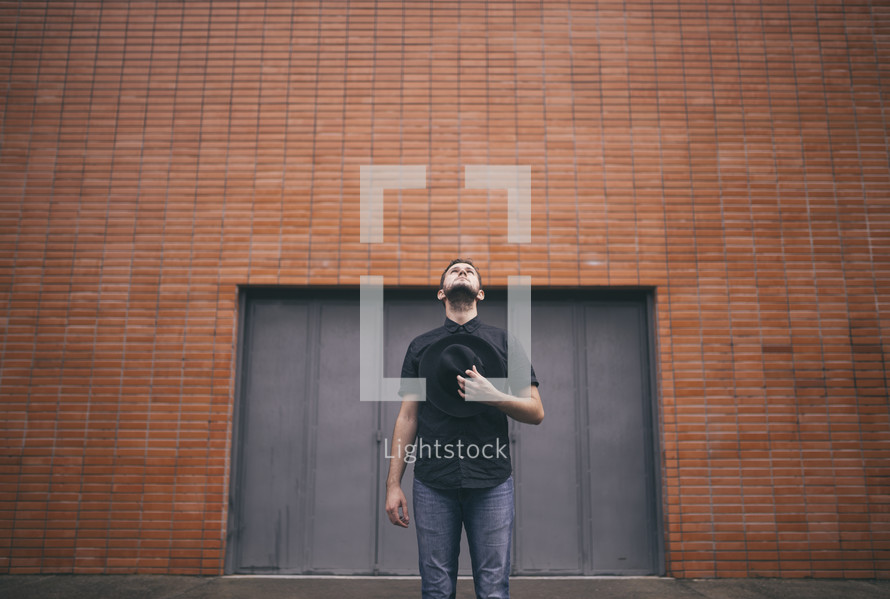man standing in front of a brick warehouse looking up