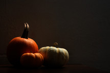 three pumpkins in shadows