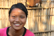 A smiling Asian girl with a bamboo fence in the background.