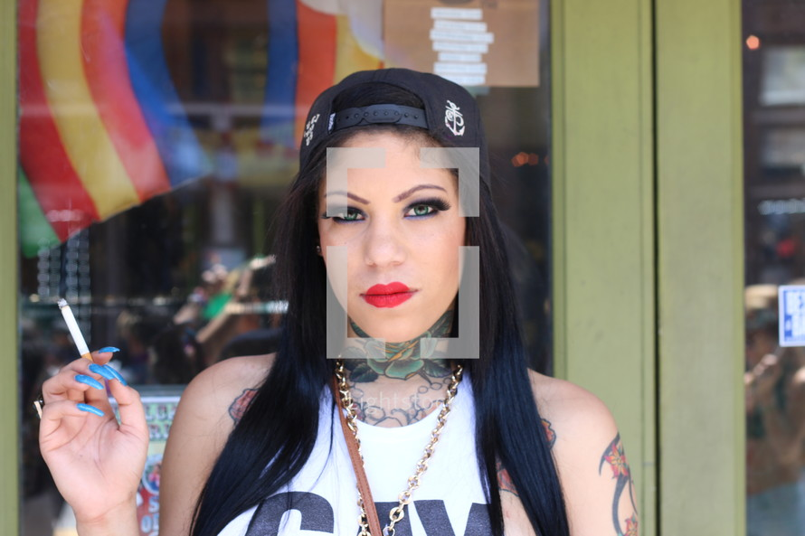 woman with long nails and tattoos smoking a cigarette