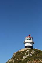 Lighthouse on a hilltop against a blue sky.