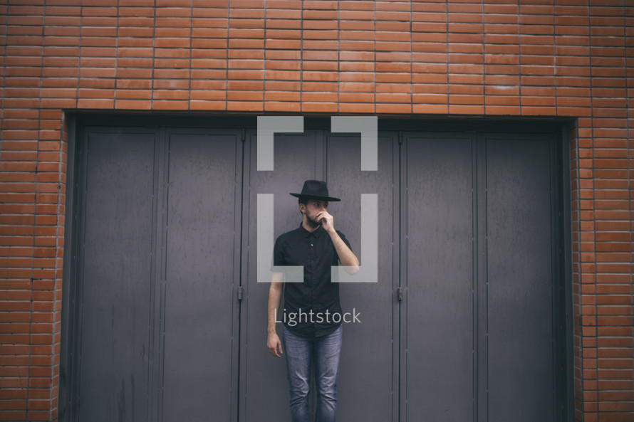 man standing in a doorway of a brick building