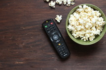 remote control and bowl of popcorn