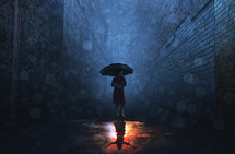 rain falling on a woman holding an umbrella at night