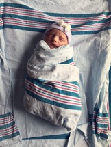A newborn infant swaddled in hospital blankets.