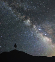 silhouette of a man on a mountaintop under stars in the night sky