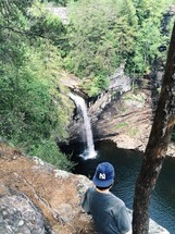 man standing at the edge of a cliff looking down at a waterfall