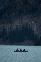 paddling a canoe on a lake  in front of a mountain