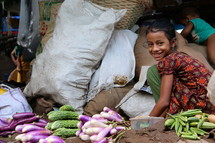 Lower caste Hindu girl sorts vegetables in a city market [For similar search Ethnic Smile Face]