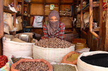 Muslim woman with a shrouded face in a market  [For similar search Ethnic Face Smile].