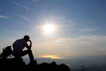 Silhouette of a man in thought / prayer sitting on a mountain top