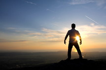 silhouette of a man standing on a mountain top at sunset / sunrise