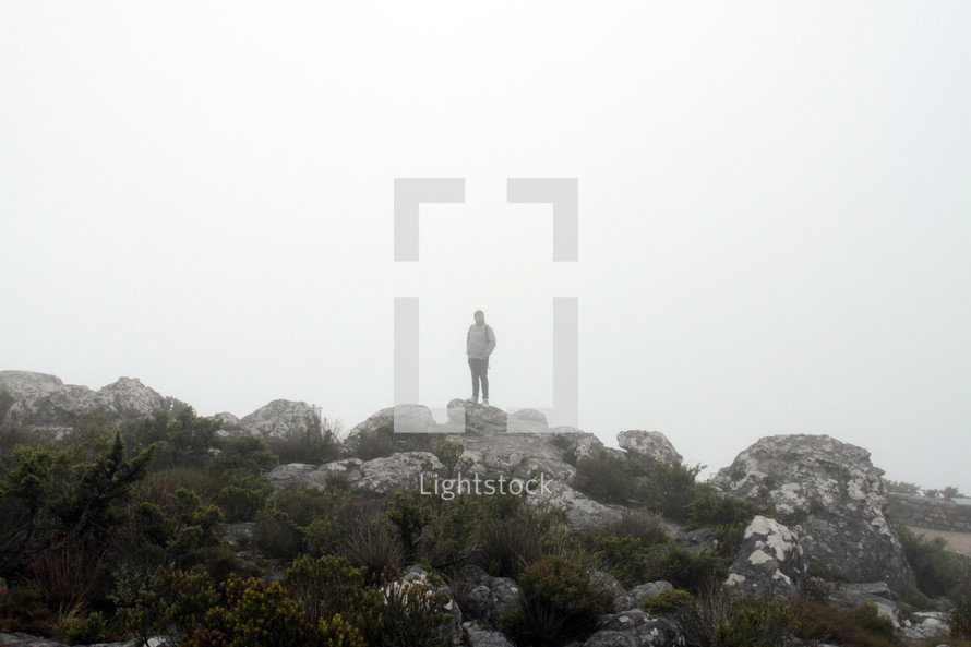 a man standing on rocks in the fog